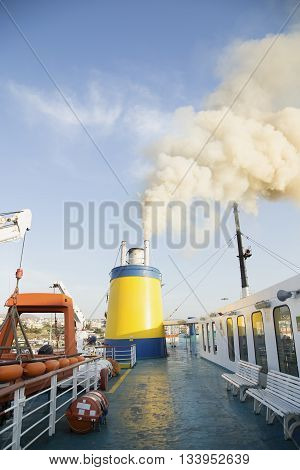Deck on a catamaran ship with the smoke from the engine