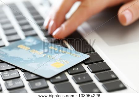 Woman hand and credit card on laptop, closeup