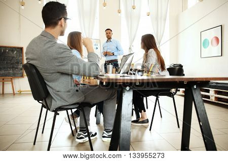 Take a look at our results Handsome young man standing near whiteboard and pointing on the chart while his coworkers listening and sitting at the table.