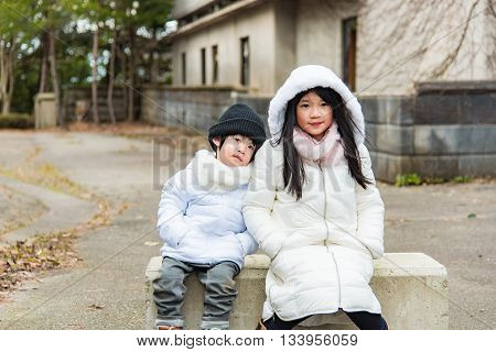 Close up of asian child wearing white jacket ion moutain in japan.