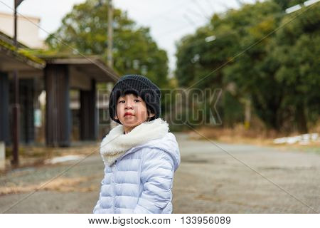 Close up of asian child wearing white jacket on moutain in japan.
