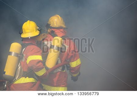 two firefighters is working surround with smoke and dust
