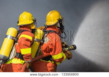 2 firefighters spraying water in fire fighting with dark smoke background