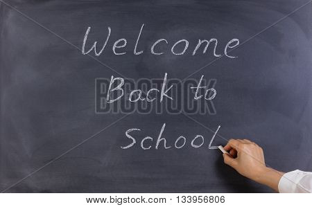 Back to school concept with female teacher hand writing on erased black chalkboard.
