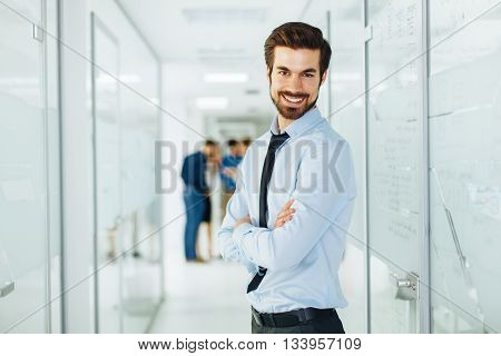Young happy businessman is posing in hallway
