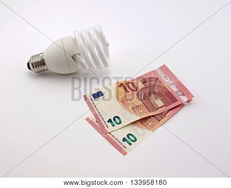 energy saving lamp and money on a white background