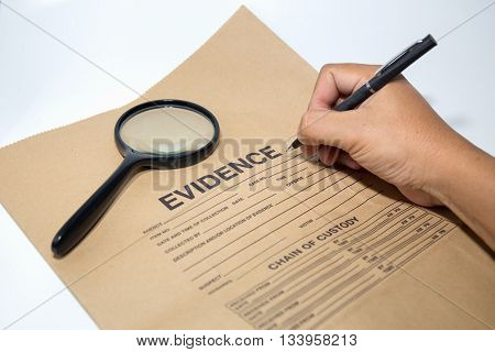 hand with pen writing on evidence paper with magnifying glass