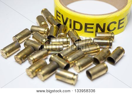 evidence tape with group of brass bullet cases on white background