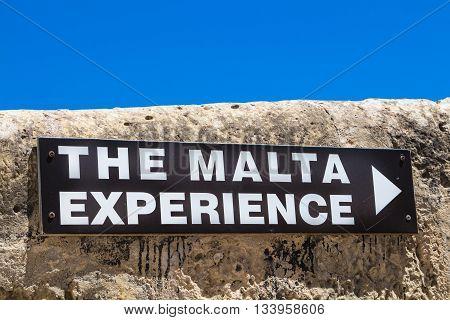 Board of the Malta Experience program - explaining the history of island Malta. Black board on the stone fence bright blue sky.