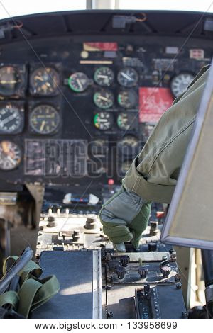 helicopter pilot hand in glove adjust knob on instrument panel in flight