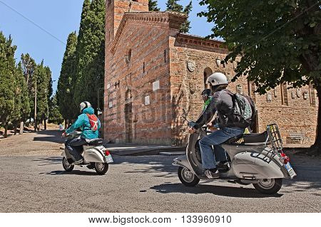 POLENTA (BERTINORO) ITALY - JUNE 5: bikers riding vintage italian scooters Vespa passing in front of the medieval church during the scooter rally