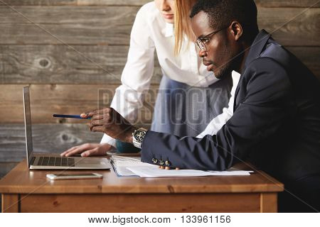 Dark-skinned Entrepreneur Sitting At Table And Pointing At Computer Screen To Find Solution With His