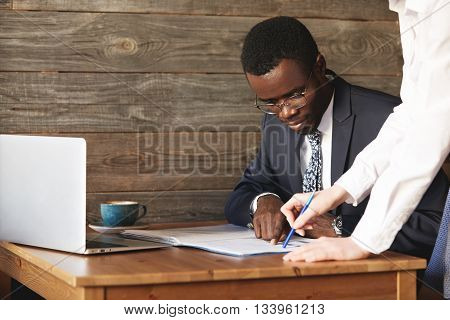 Focused African American Businessman Checking Papers With His Personal Assistant In White Shirt. You