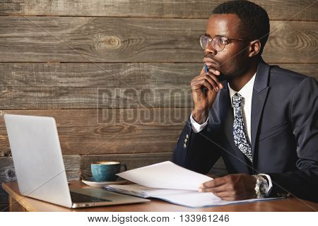 Handsome Young African Man Wearing Formal Suit Sitting At A Coffee Shop With Pensive Look, Thinking