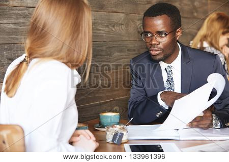 African Boss Conducting An Interview With Redhead Caucasian Woman, Holding Job Application And Liste