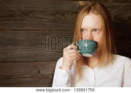 Young Blond Office Girl Drinking Coffee In Stylish Café. Caucasian Female Business-lady Looking