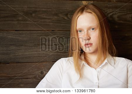 Full Face Beautiful Portrait Of Beautiful And Young Caucasian Girl On Wooden Background. Blond Offic