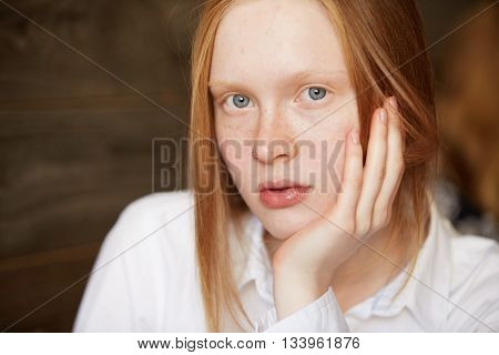 Close Up Portrait Of Caucasian Blue-eyed Girl With Blond Long Hair Looking At Camera. Young Female R
