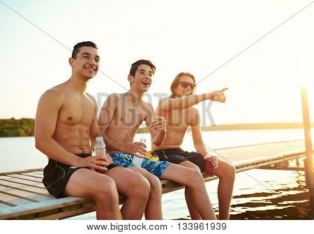 Three Male Friends Enjoying A Drink At Sunset