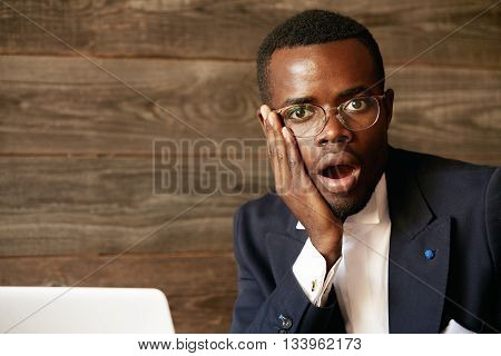 Close Up Portrait Of Handsome Young African Corporate Worker Who Is Scared, Shocked Or Astonished By