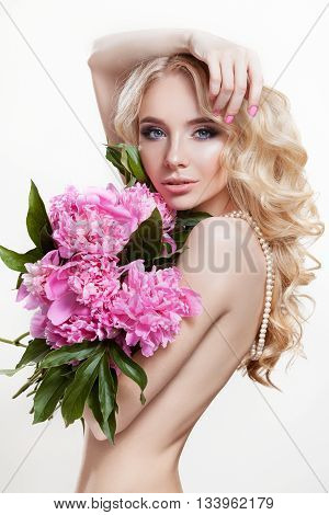 Portrait of cute young girl with beautiful makeup . Blond hair wavy curls. Beauty clean skin . Photographed in studio on a white background. The lady holding a bouquet of pink peonies. Light Tone .