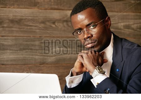 Young African Office Worker Wearing Elegant Formal Wear And Glasses While Using Wireless Internet Co