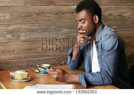 Portrait Of Handsome Young Dark-skinned Man In Casual Clothes, Holding Electronic Gadget, Looking At