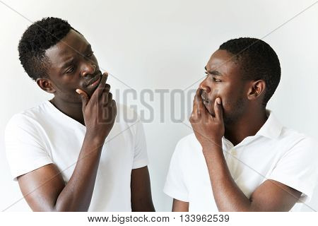 Portrait Of Two Cautious And Thoughtful Black Guys Wearing White T-shirts Looking At Each Other With