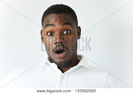Close Up Of Amazed Young African American Man In White Polo Shirt, Having Fun Indoor, Looking At The