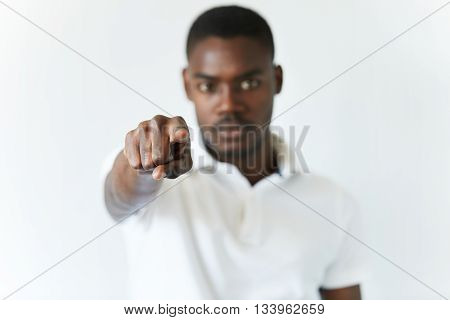 Isolated Studio Portrait Of Young Dark-skinned Student In White Shirt, Pointing At The Viewer, Looki