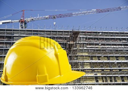 Yellow safety helmet with construction site background