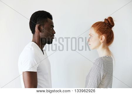 Sideways Portrait Of A Couple Looking Each Other In The Eyes On White Background. Afro Man Standing