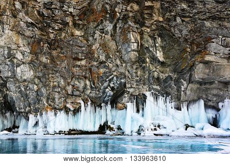 Rock formation with iced skirt and frozen lake beneath