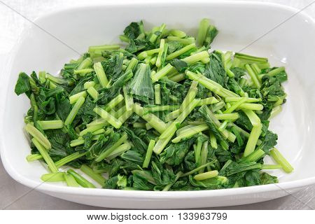 green boiled bog choy vegetable in white bowl
