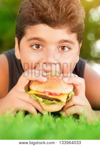 Portrait of a hungry teen boy lying down on fresh green grass and with pleasure eating burger, tasty, but unhealthy food