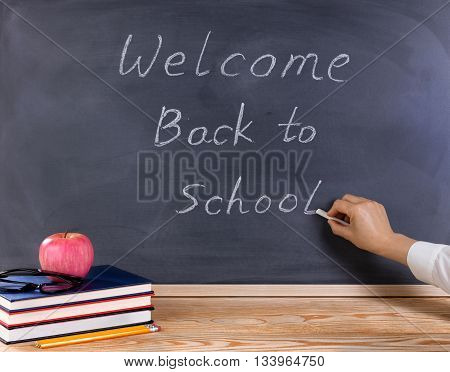 Teacher hand writing on erased black chalkboard. Desktop with books apple pencils and reading glasses in forefront. Back to school concept.