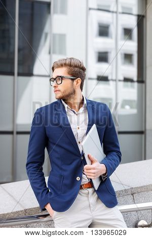 Attractive young man is waiting for someone. He is standing outdoors and looking aside with anticipation. The guy is holding a laptop