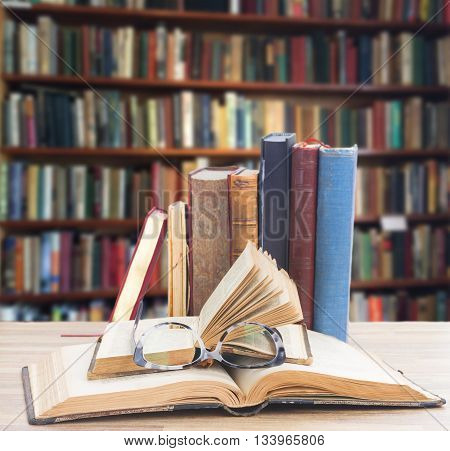 Books and glasses on wooden table desktop in library