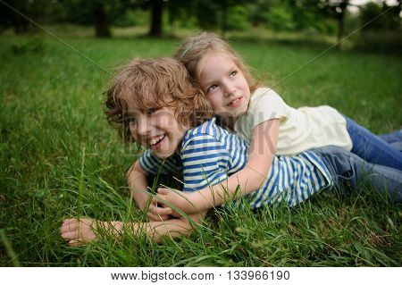 The brother and the sister play on a green lawn. The girl embraces the brother. They lie on a green grass. Children have fair hair and nice faces. They like to spend time together.