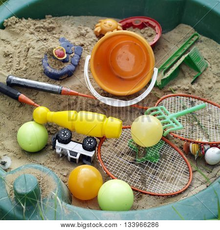 Tennis rackets and other toys in the sandbox outdoor still concept of summer activity and sport