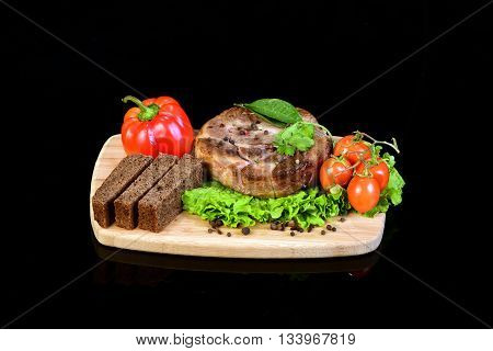 Delicious steak medallion with lettuce, pepper, cherry tomatoes and three slices of bread on a wooden cutting board. Black background with reflection underneath