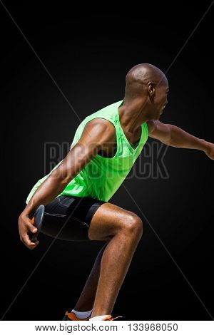 Rear view of sportsman throwing a discus on a black background