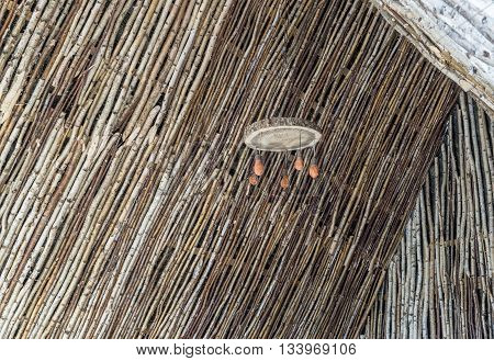 Wooden ceiling lamp is in hut of birch trunks