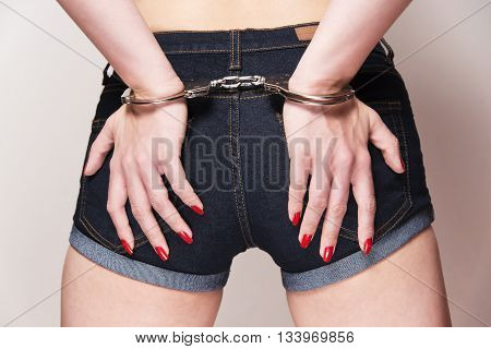sexy woman wearing denim shorts with hands on her backside wearing a pair of handcuffs