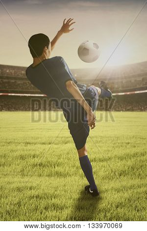Portrait of young football player kicking a ball on the soccer field