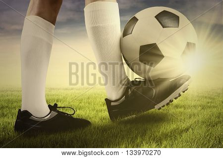 Foot of soccer player playing a ball on the grass in the morning at sunrise time