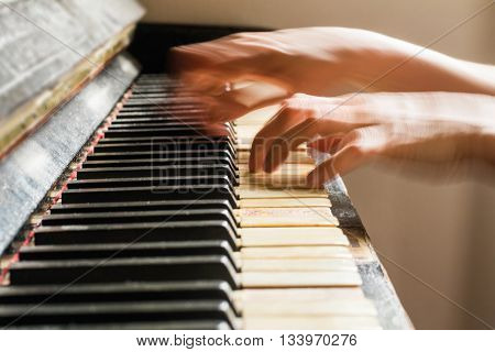 Old rusty piano, selective focus, woman's hands on keyboard, intentionally blurred motion