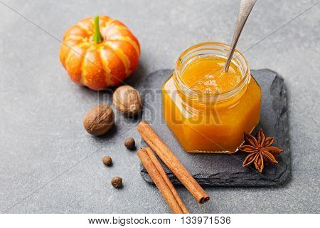 Pumpkin confiture jam sauce with spices on stone table.