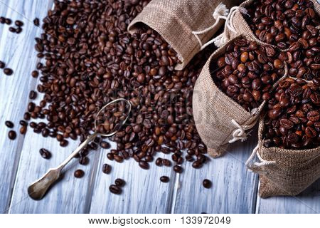 Jute Bags Filled With Coffee And Silver Spoon