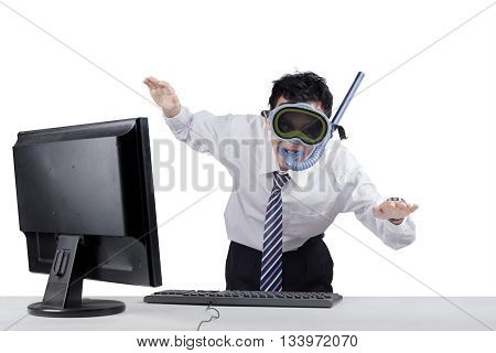Strange businessman wearing goggles and snorkel with computer on desk posing to swim